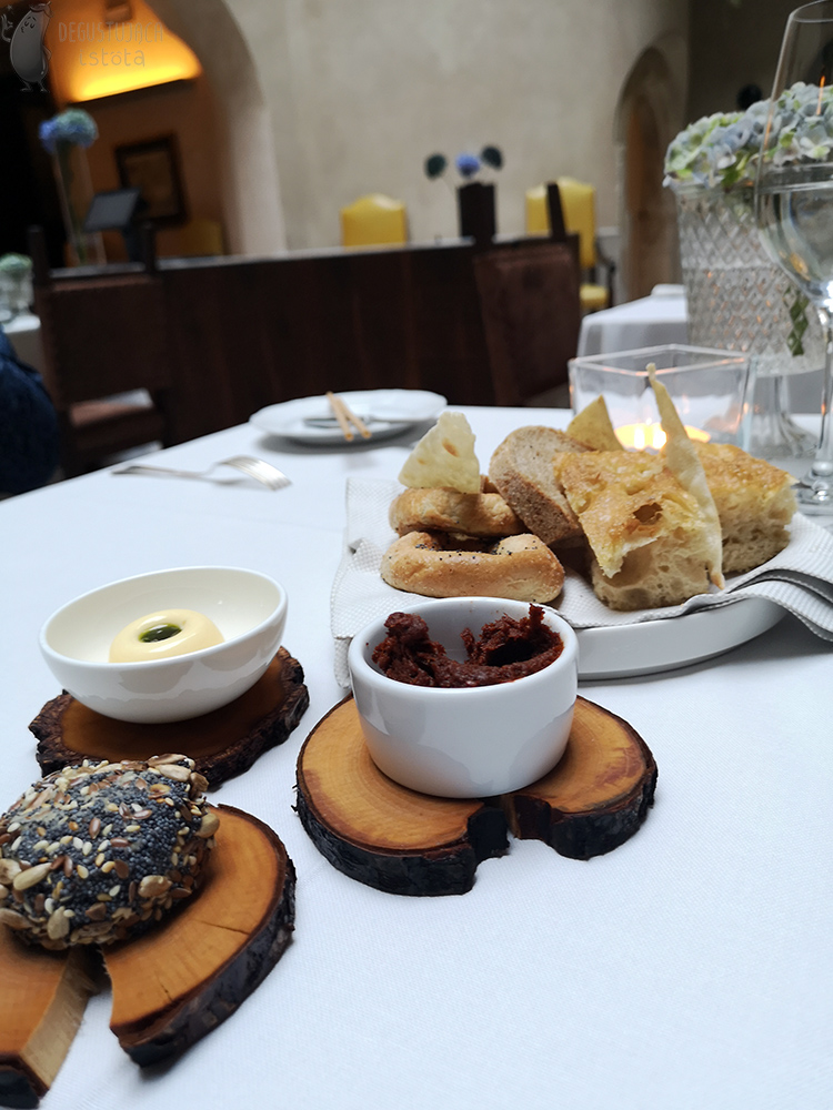 On the table on three small woods lie two white bowls. One with red tomato paste, the other with butter. On the third wood lies a disc of lard from beans, coated in poppy seeds and grains. In the background, various breads lie on a white plate and napkin.
