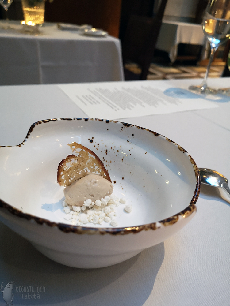 In a deep white bowl with a brown rim, lies a portion of light brown ice cream with a crunch in the middle and a white crumble.