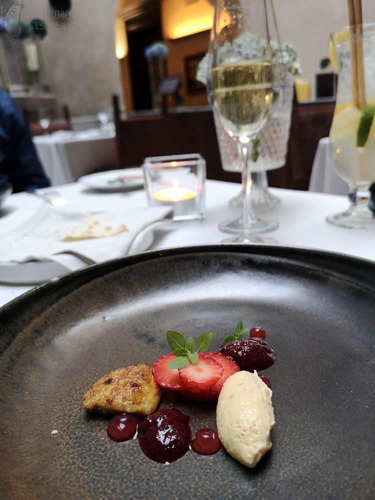 On a flat, dark gray plate lies a piece of fried liver, a dose of pate, slices of strawberries, two servings of strawberry chutney and dots of pink gel.