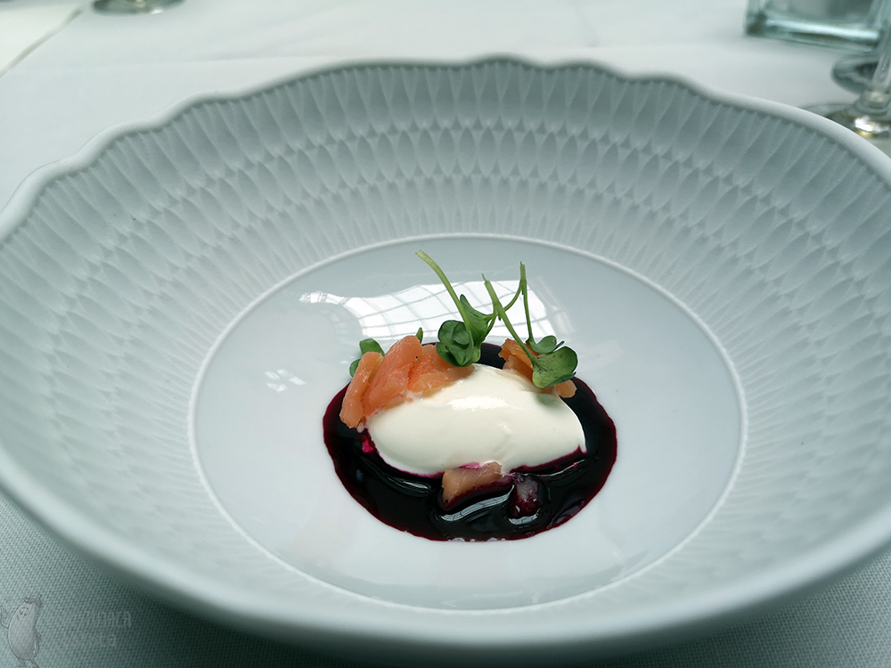 On a blue plate lies a portion of white ice cream surrounded by beet consomme and garnished with pieces of salmon.