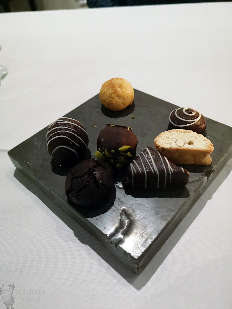 Chocolate pralines and cookies are arranged on a black rectangular stone.