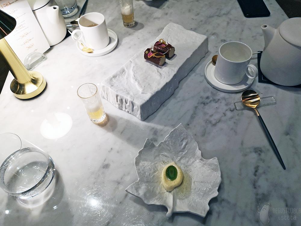 Zdjęcie marmurowego stołu na którym ułożone są powyższe słodycze oraz kieliszki z żółtym kwasem jabłkowym.