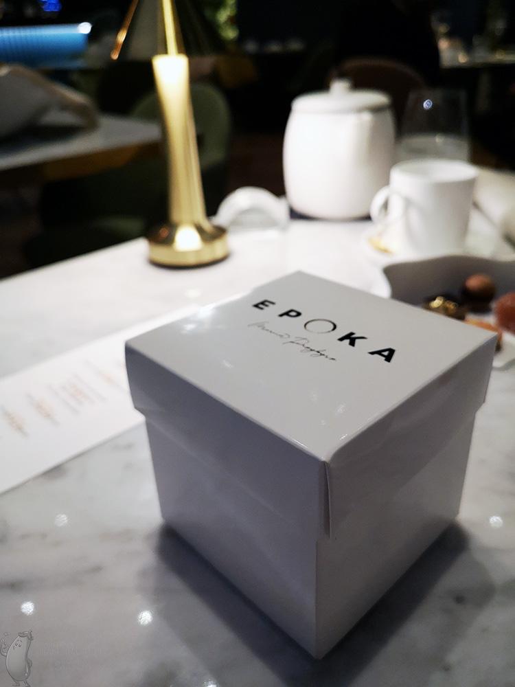 """Białe pudełko ze złotym napisem """"Epoka, Marcin Przybysz"""" położone na stole."""