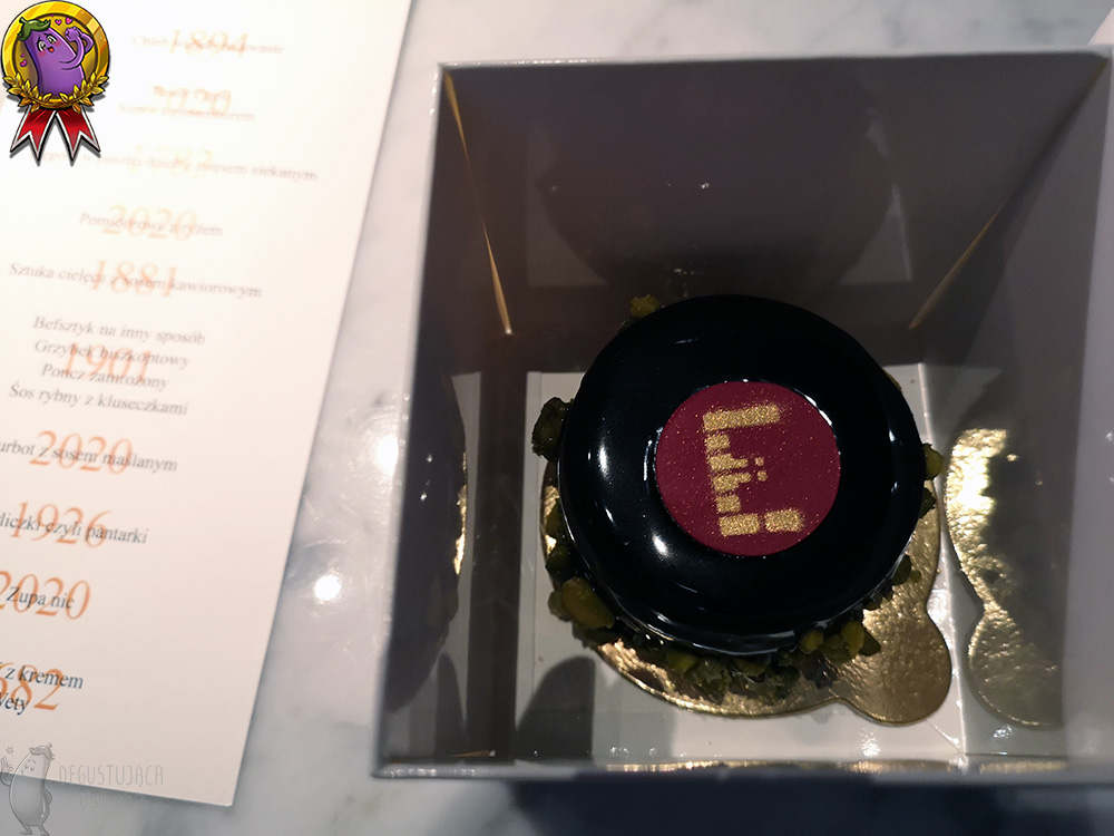 The inside of the box. Chocolate-wrapped cake on a golden base, with golden E in the middle of the cake written on a red chocolate disc.