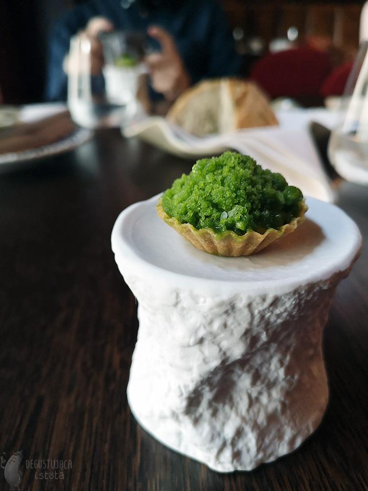 A small tartlet with green granita lies on a white ceramic pedestal.
