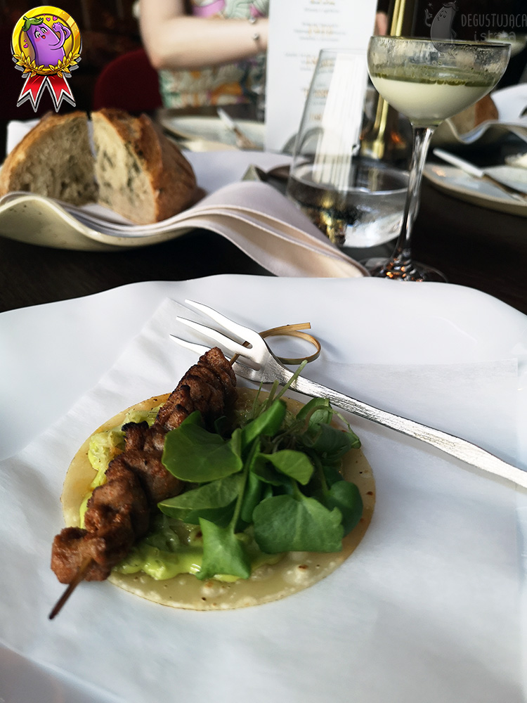 On a flat white plate, a pancake is placed on white paper, a salad with dressing is placed on it and a meat skewer is placed on the salad. A small fork is placed at the top of a wooden stick from the skewer. In the background is a glass of Ayran.