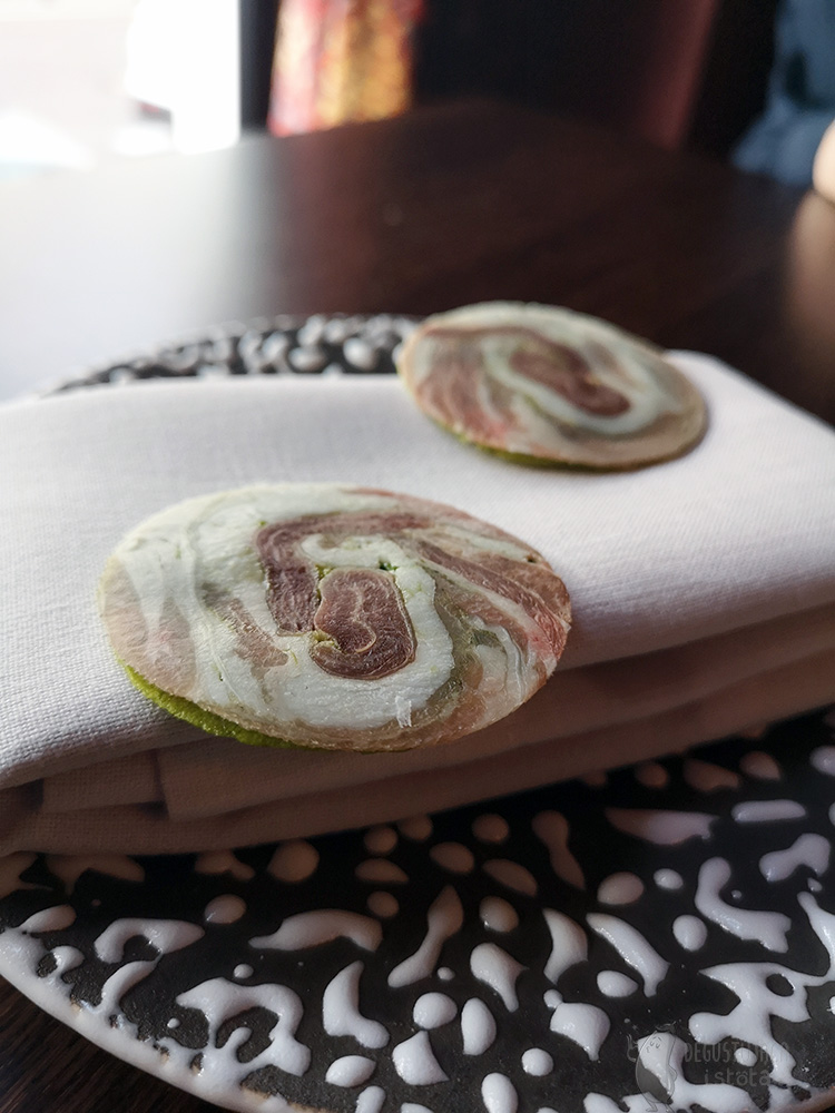 On a black and white plate, on a napkin, there are two discs of thin wafers on which a ham is placed. The same wafers as above only from a different angle.