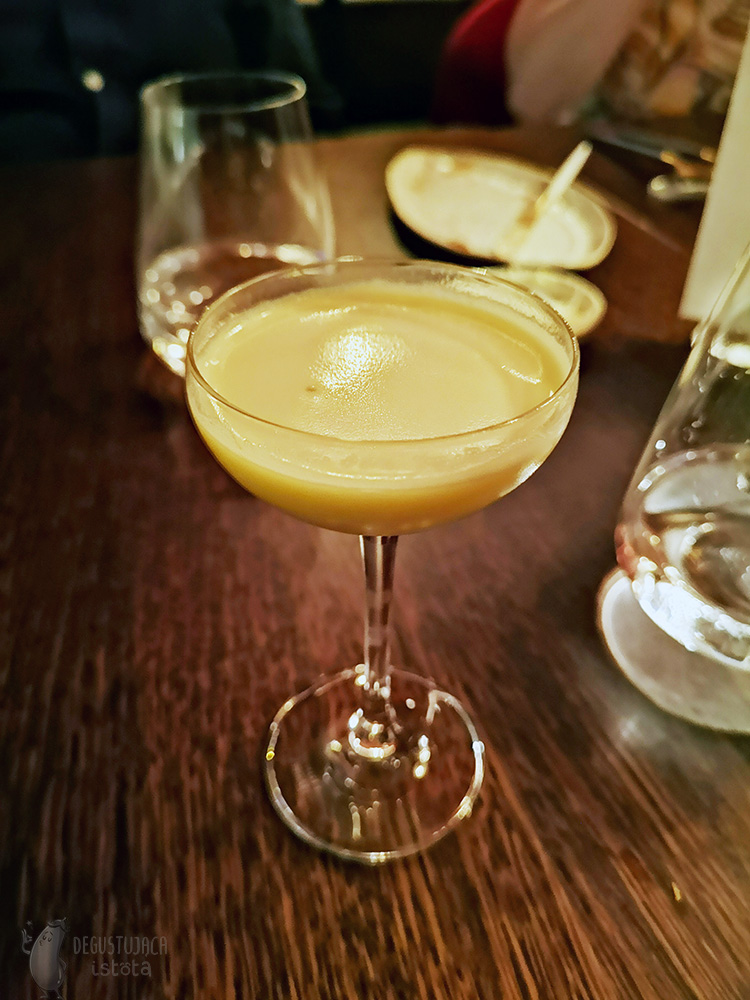A glass with a creamy yellow liquid.