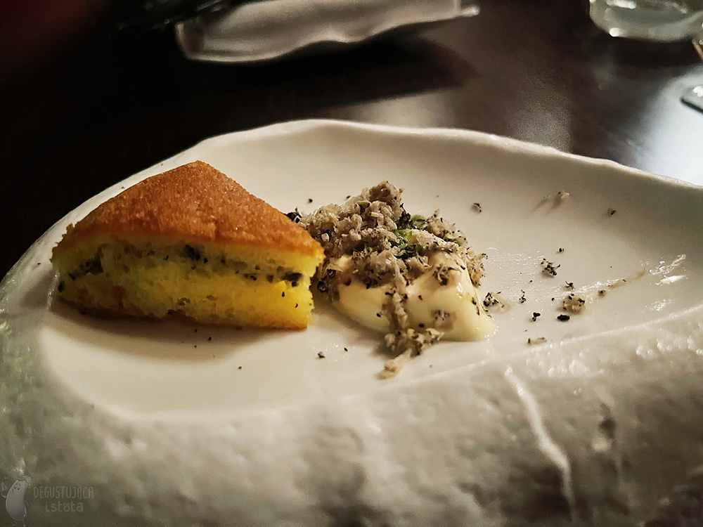 On a white plate, stylized on marble, there is a white ice cream topped with coarse grated black truffle. Next to it, on the same plate, is a triangular piece of potato cake.