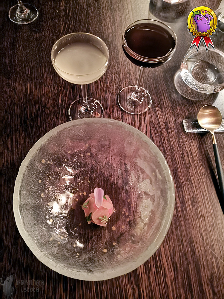 In a deep glass, In a deep transparent glass bowl, pink rhubarb slices with a rose petal on top lie arranged in the middle. Two glasses stand next to it. One with a yellow drink, the other with dark brown rooibos.