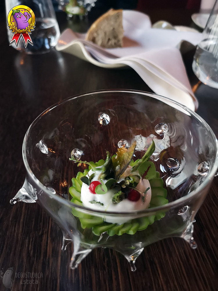A glass bowl resembling a sea urchin. Arranged slices of green asparagus in the center, on which is a white foam decorated with leaves and two red balls.