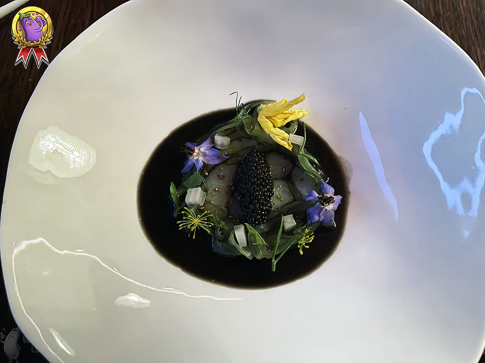 Pieces of white fish are placed in a large, white plate, surrounded by black powder and arranged in the shape of a circle. There is a portion of sturgeon caviar on the fish. There is a black sauce around the fish and it is decorated with purple and yellow flowers and green leaves.