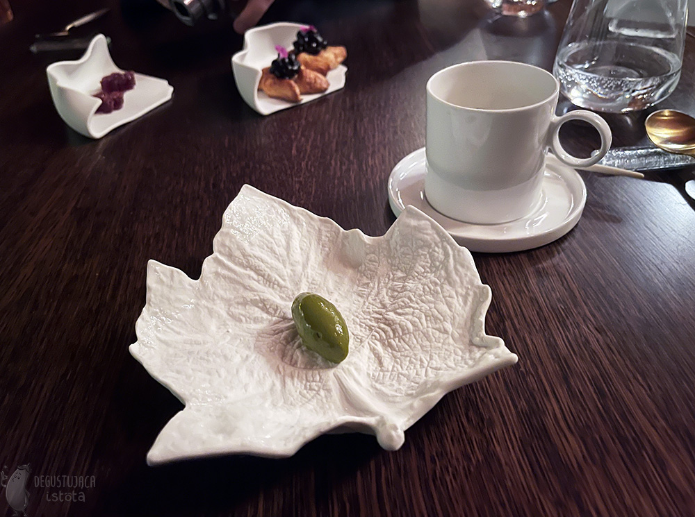A white plate in the shape of a maple leaf with a portion of green ice cream on it. Next to it a white mug, and in the background two small plates. One with two danish pastry baked with berries, the other with two pink jellies in sugar in the shape of flowers.