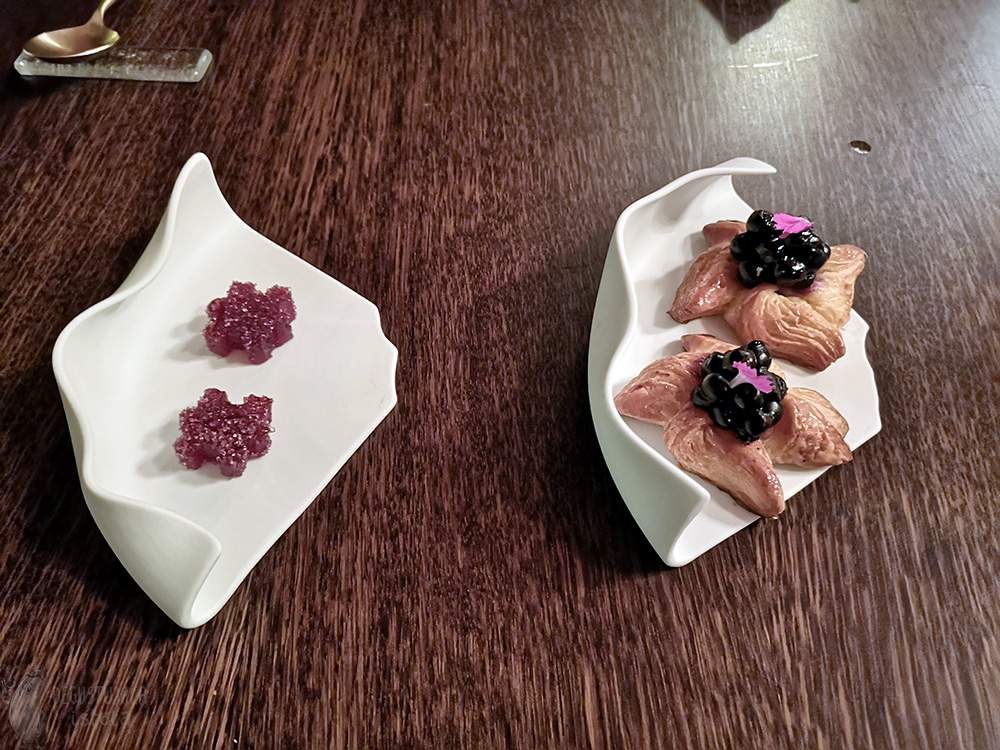 Two small saucers. One with two blueberry danish pastries, the other with two pink flower-shaped sugar jellies.