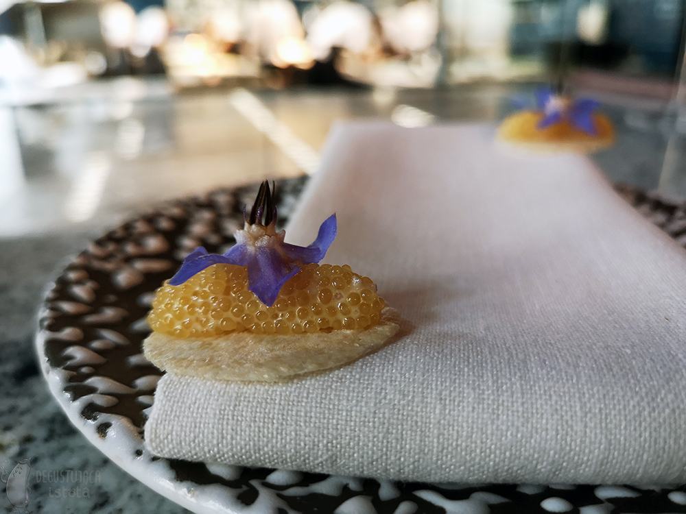 On a black plate with white dots, on a white napkin lies a yellow disk with orange roe and a purple flower on top.