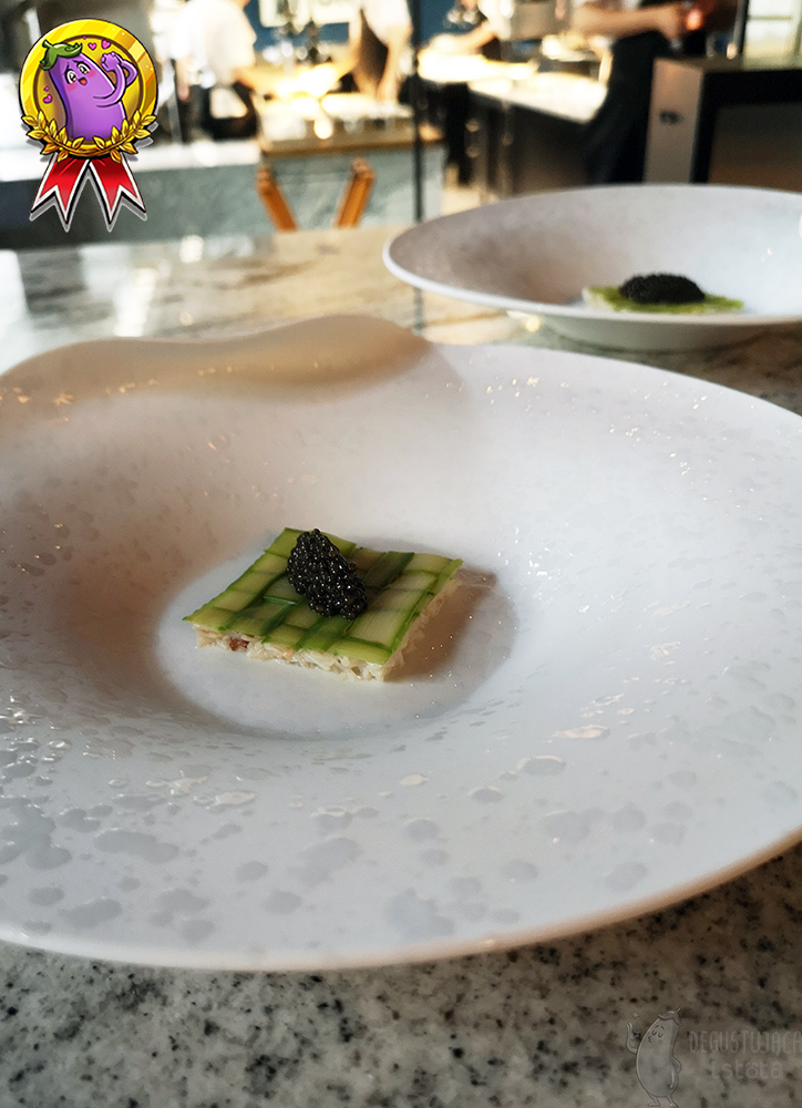 White large plate in the center of which the grid of slices of green asparagus on which there is a portion of caviar is located.