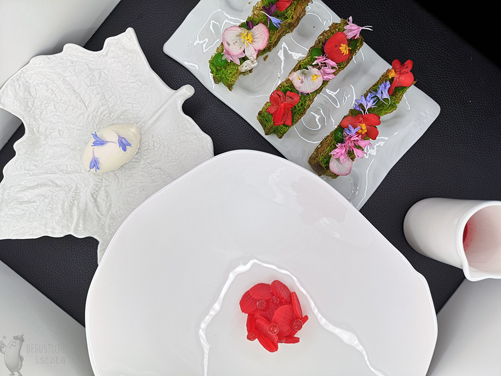 Various white dishes arranged tightly. On the leaf-shaped plate lies white sorbet decorated with blue flowers. On the second platter there are 3 green waffles decorated with flowers. There is a red, thick compote in the small jug. Rhubarb rings with red balls are arranged in a hemisphere on the largest flat plate.