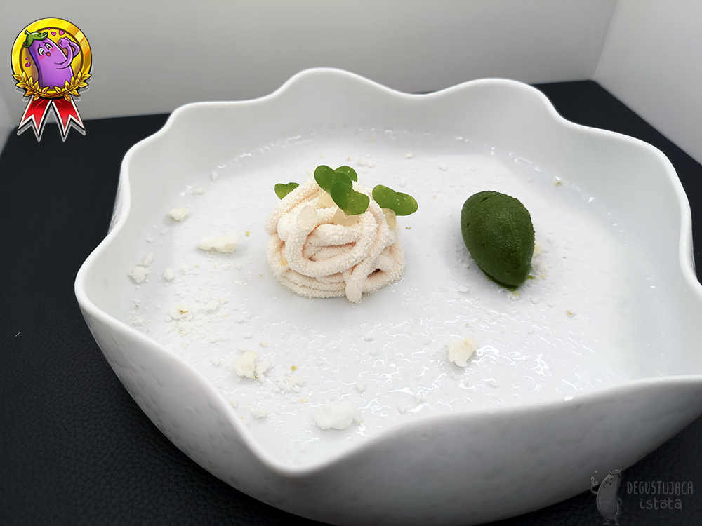 In a wide white bowl with a wavy edge lies a white portion of cream sprinkled with white chocolate. Next to it lies a dark green sorbet. White lime pebbles are crushed around.