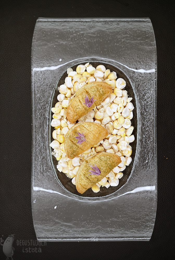 On a glass platter filled with freeze-dried two Patties in the shape of dumplings lay in the corn. Garnished with purple chives flowers.