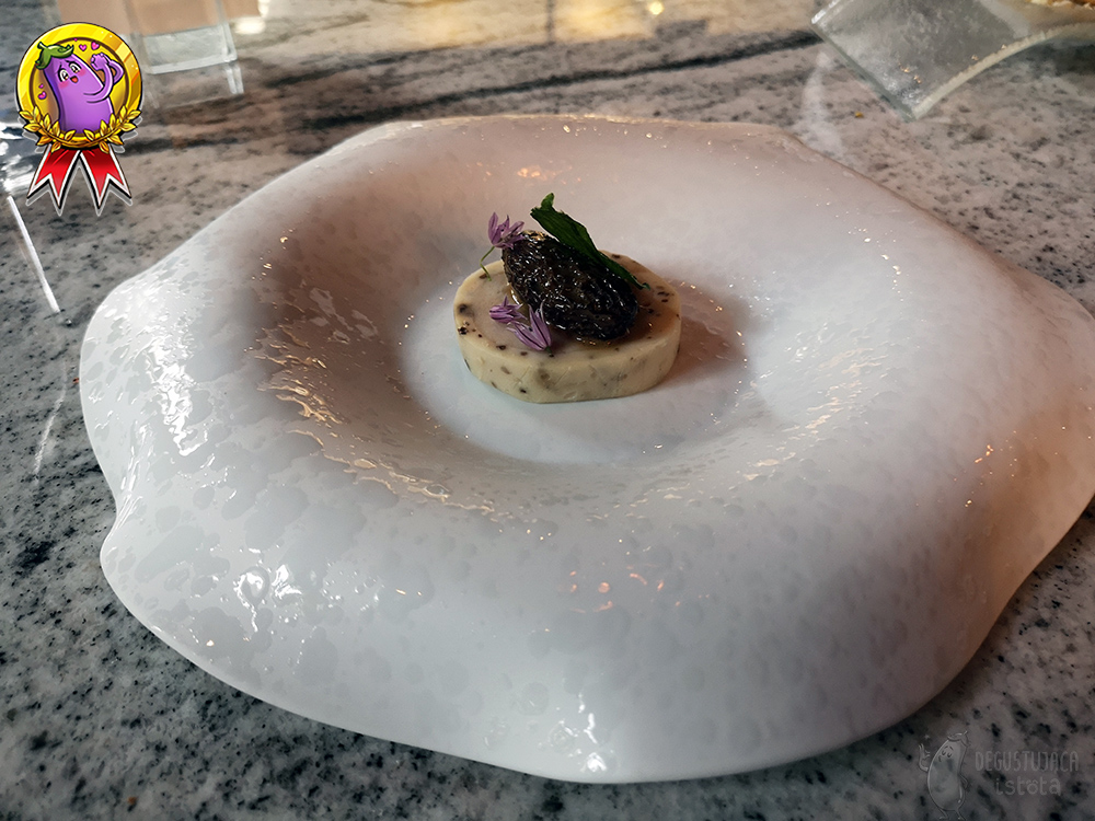 On white, in a deep plate with irregular edges, a round portion of guinea fowl meat is applied. On its top there is morchella, which is covered by a garlic leaf. The whole dish is decorated with purple chives flowers.