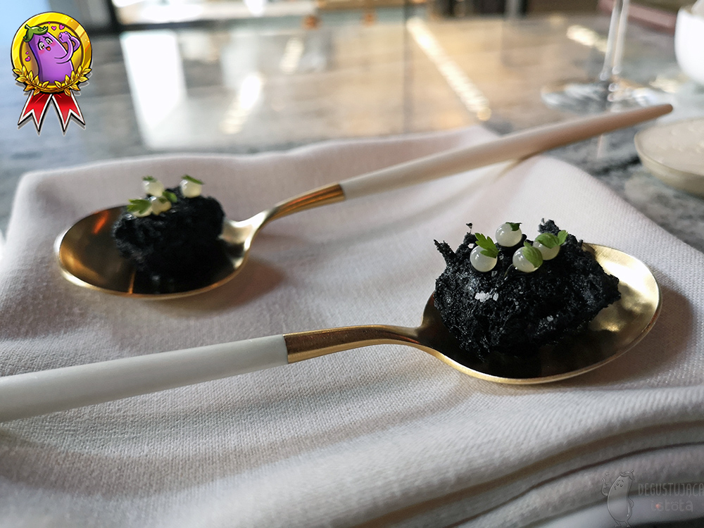 Snails lie on golden-white teaspoons in black tempura, decorated with white caviar balls.
