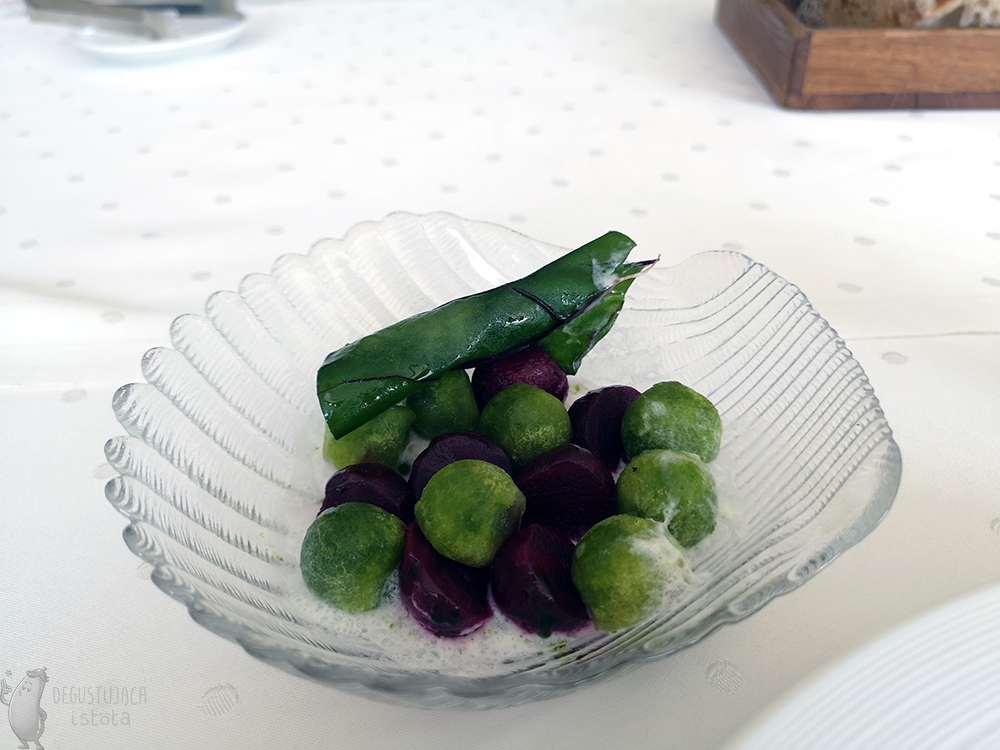 In a glass bowl in the The shell-shaped bowl contains red and green beet and apple balls. Horseradish sauce can be seen at the bottom.