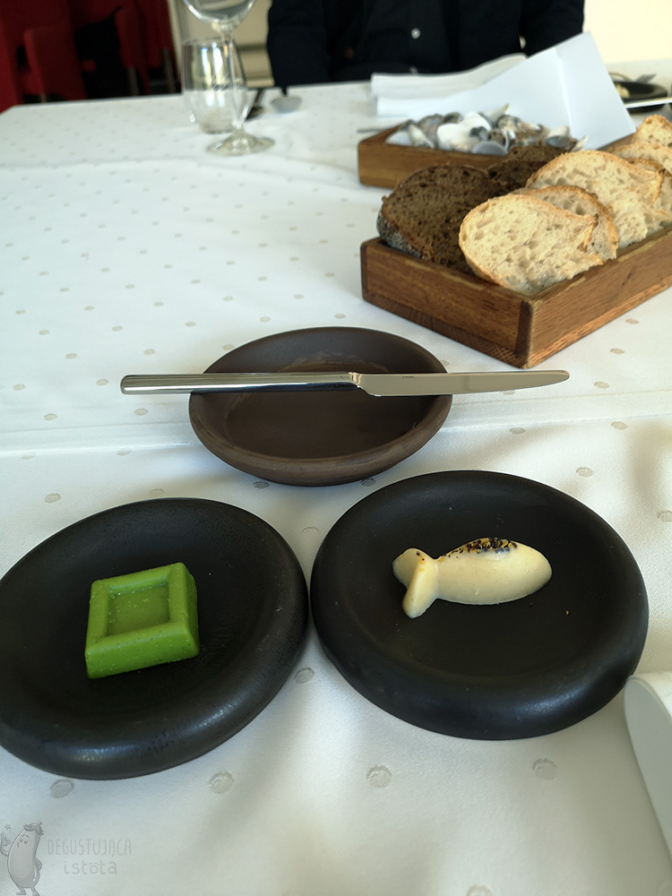 On a table covered with a white tablecloth are 3 black plates and a wooden container with slices of light and dark bread. On one black plate is green butter in the shape of a square and on the second plate is burnt butter in the shape of a fish. On the third plate is a butter knife.