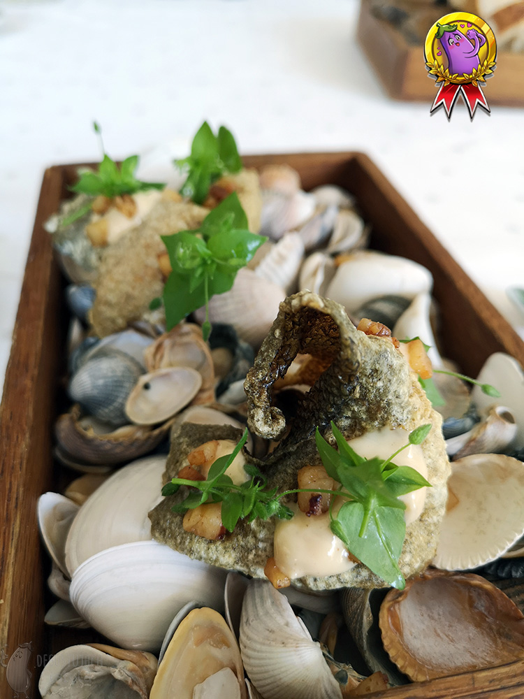 In a small wooden box, there are seashells on which crisps with trout skin on which are arranged crisps of trout skin with dots of mayonnaise and leaves of chickweed.