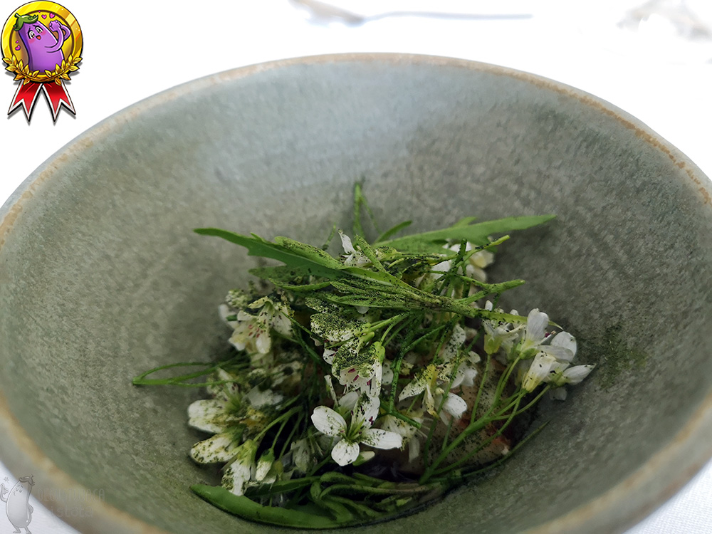 The dark grey bowl is filled with white flowers and stems of cress sprinkled with green powder.