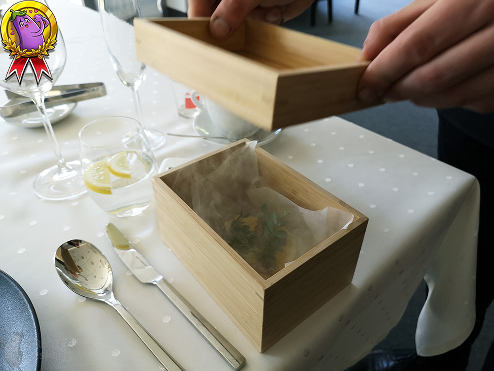 On the table, there is a small box in which there is a tartare with a dried yolk sprinkled on top. Smoke is coming out of the box whose lid has been lifted.