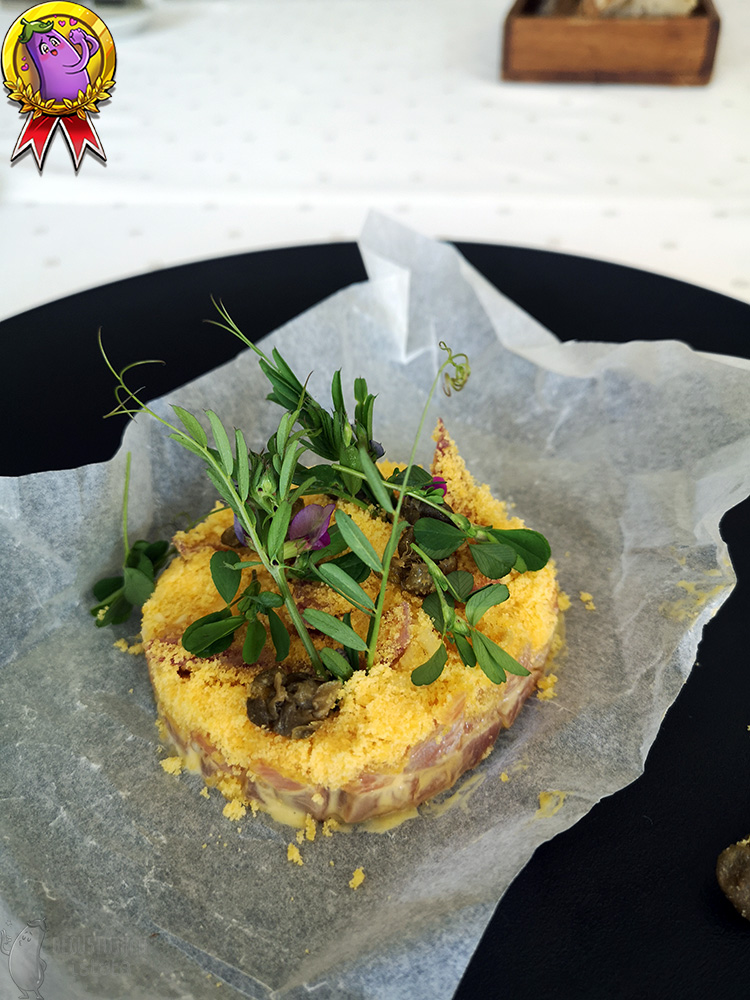 On a large flat plate, a portion of tartare sprinkled with egg yolk and garnished with green leaves.