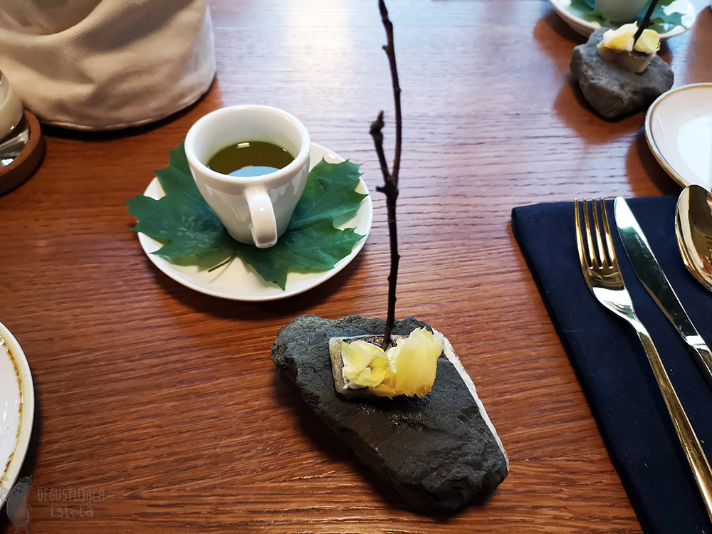 White coffee cup filled with orange and green liquid. On a saucer and under the cup lies a green maple leaf. Next to it on a stone lies a piece of fish pierced with a stick.