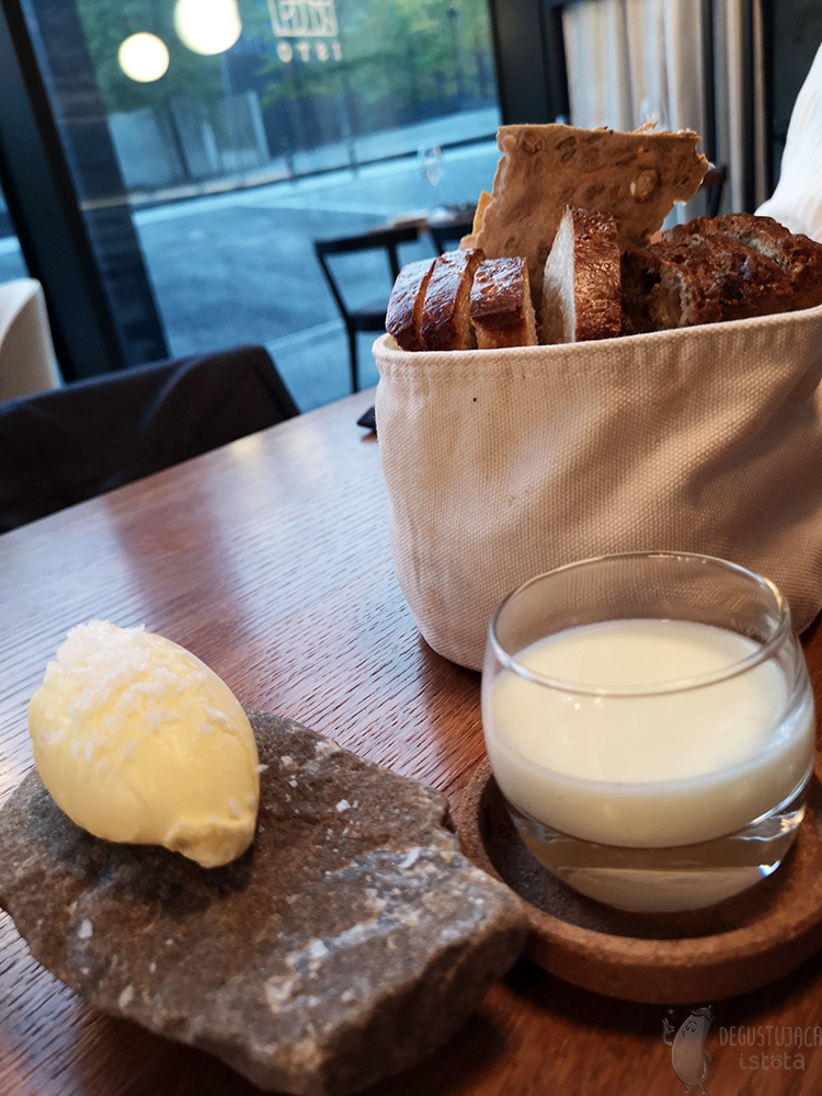 On a wooden table lies a cloth bag filled with bread. Next to it lies a dark stone with a portion of yellow butter sprinkled with coarse salt. In a low glass between the stone and the sack is a white espuma.