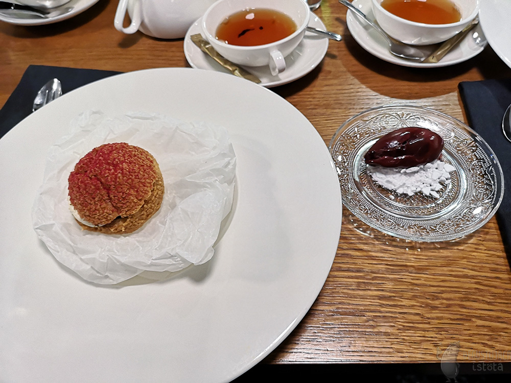 On the table lie white tea cups and a large white flat plate with a puff in the middle. The puff lies on rolled up baking paper. It is sprinkled with red powder on top. On a transparent plate next to the plate with the puff, lies purple red ice cream on crumbled white meringue.