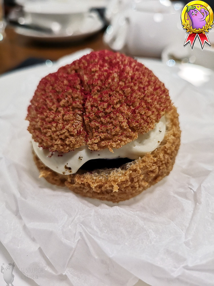 A large, white, flat plate with a puff in the center. The puff lies on rolled up baking paper. The top is sprinkled with red powdered sugar.