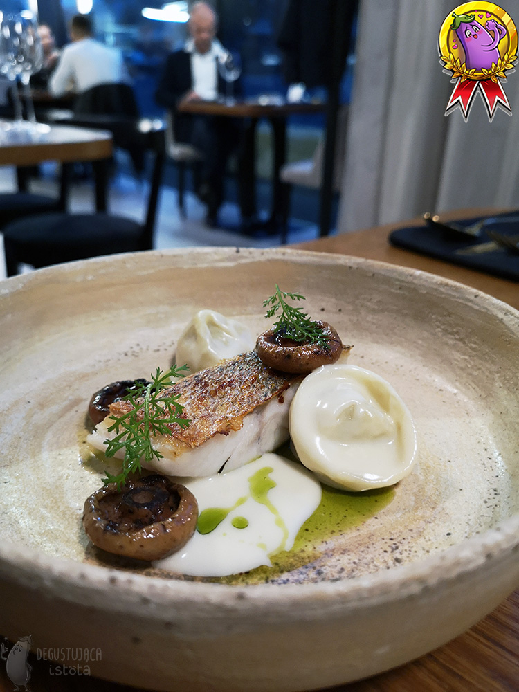In a gray, flat plate with a high edge lies a piece of white fish with the skin baked up. Next to the fish there are hats of fried red pine mushrooms and two ravioli. The whole dish is covered with a thick white sauce and drizzled with green olive oil.