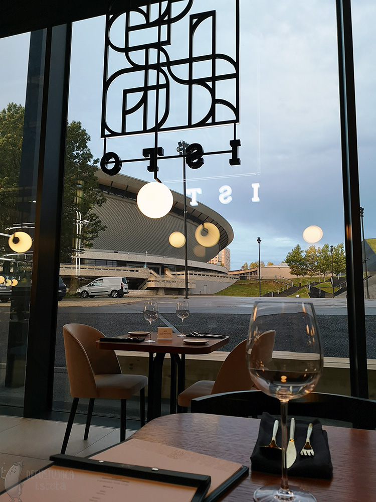 You can see part of the Spodek through the windows of the restaurant with the Isto logo. The sky is overcast and the evening is coming.