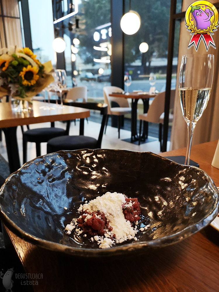 In a dark, glossy, deep plate lies a portion of tartare covered with white chunks of frozen cheese.