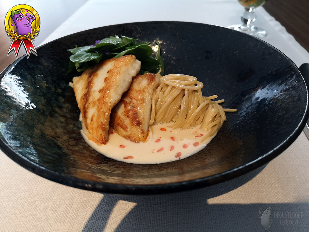 In a black shiny plate lies a coiled linguini. There are two pieces of turbot and baby spinach leaves on the pasta.