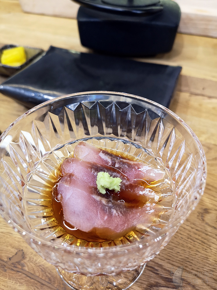 In a transparent dish are arranged three thin slices of raw fish. They are doused in dark sauce and garnished on top, with a small portion of grated green wasabi.
