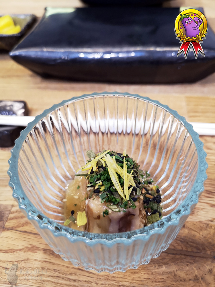 In a transparent container there is a piece of eggplant peeled and garnished with spring onions and strips of lemon zest.