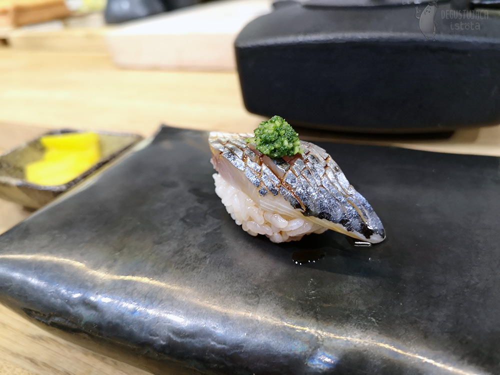 Nigiri with a piece of mackerel with skin, cut finely and a portion of the green mixture of ginger and spring on top.