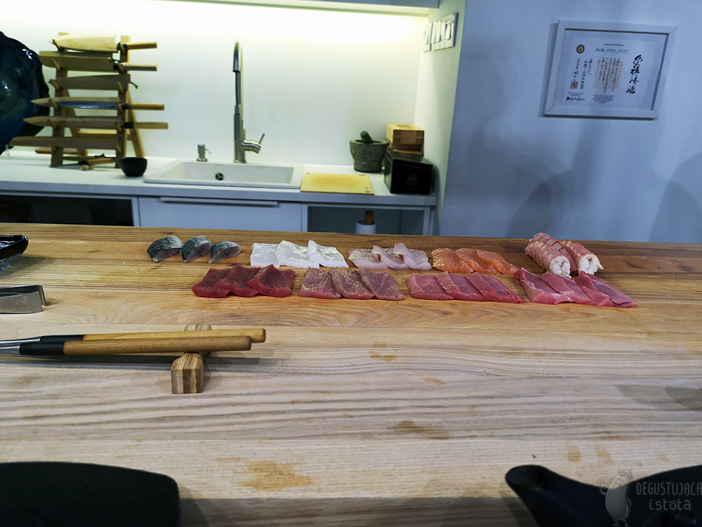 On a large board are prepared 3 pieces of each type of fish or seafood.