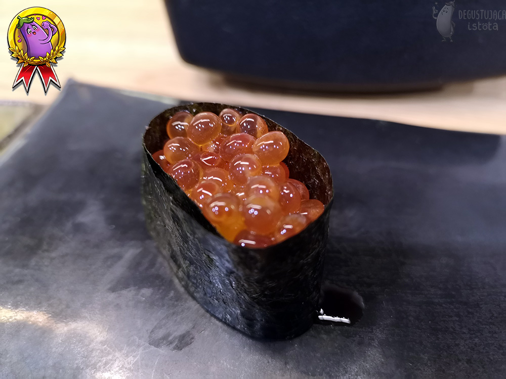 Sushi wrapped in nori algae with a portion of Ikura on top.
