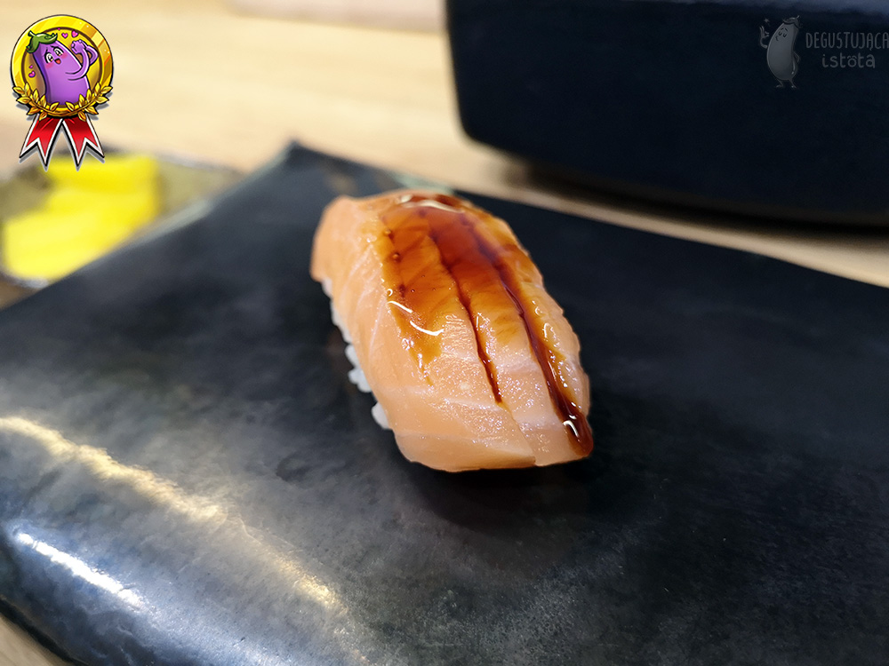 Nigiri with salmon punched on top and topped with sauce.