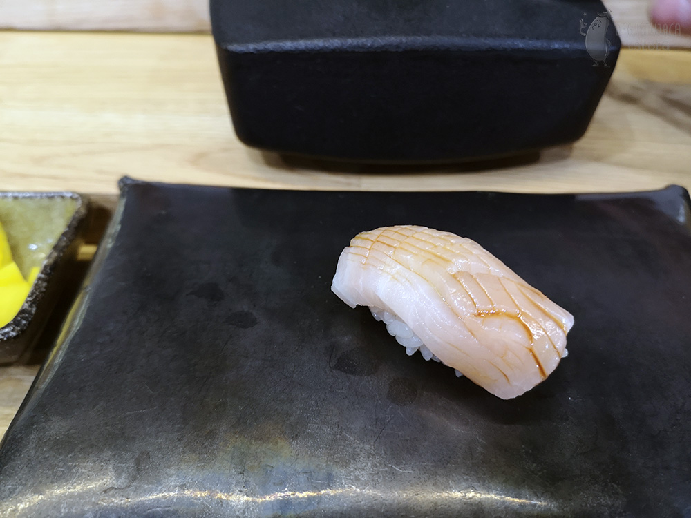Nigiri with light fish topped with sauce.