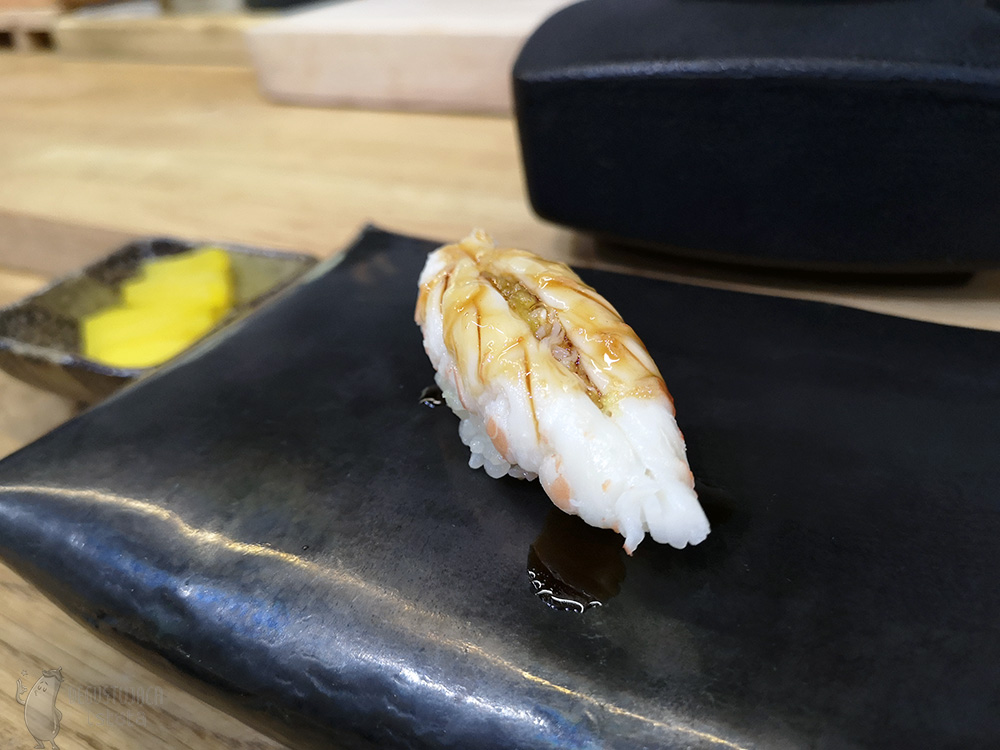Nigiri with shrimp laid out flat. The shrimp is white in color and topped with a dark sauce.