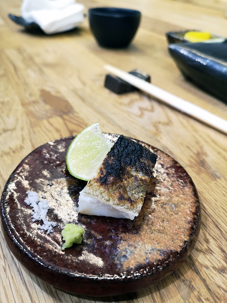 On a dark brown, small plate is a piece of fish with burnt skin. Next to it lies a slice of lime, some salt and grated wasabi.
