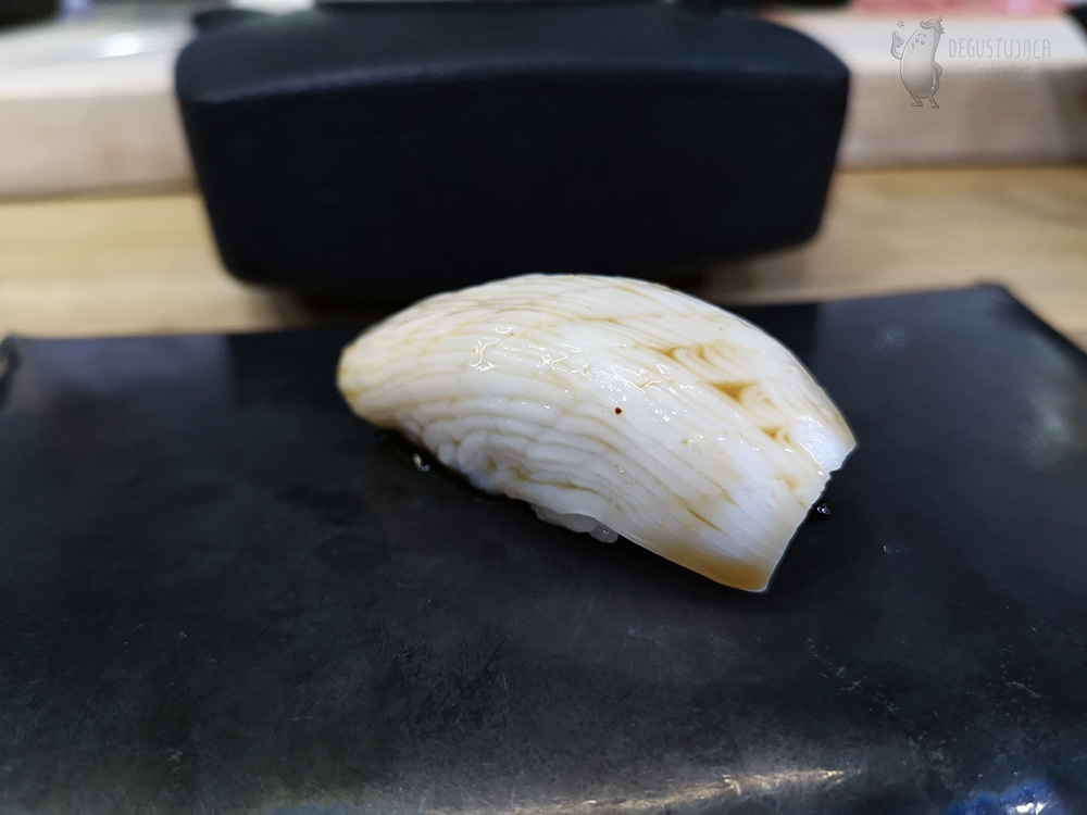 A piece of light squid, topped with sauce and placed on rice.