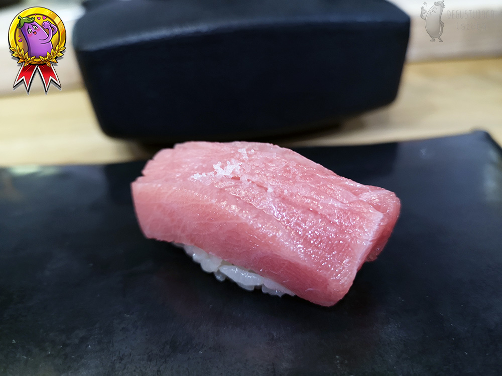 Nigiri with a light marbled tuna part with a little salt on top.